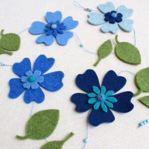 Ghirlanda primevarile con fiori azzurri e foglie - Cose di Laura creatività in feltro