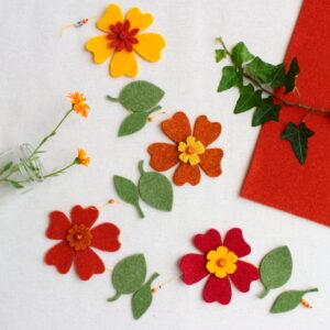 Ghirlanda primevarile con fiori giallo/arancio e foglie - Cose di Laura creatività in feltro